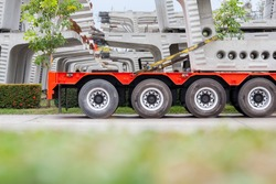 Trailer truck carrying prestressed concrete segment. Transportation of structure member from construction yard to site.