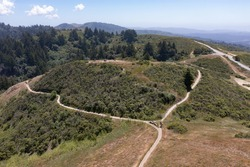 Trails meander through the vegetation-covered hills of the East Bay, just a few miles from San Francisco Bay in Northern California. This area provides open spaces for hikers and bikers.