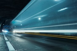 Trails of car headlights passing quickly through the highway tunnel in perspective.