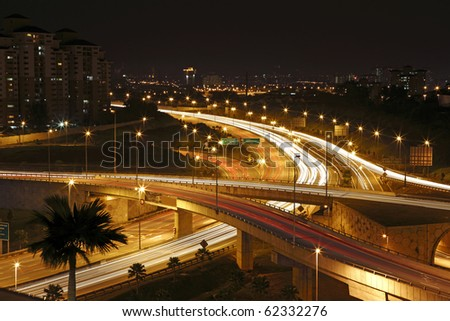 Trails of light left by vehicles on a intricate motor highway system at night.