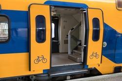 Train at Dutch railway platform with open doors