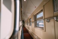 Train carriage, empty corridor with windows and compartment doors on a sunny day