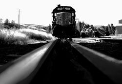 train coming toward you on tracks, grain elevators in background