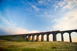 Train crosses the famous Ribblehead Viaduct. The Ribblehead Viaduct or Batty Moss Viaduct carries the Settle–Carlisle Railway across Batty Moss in the valley of the River Ribble at Ribblehead.