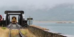 Train crossing the Mawddach estuary on Barmouth railway bridge on a grey cloudy day wide crop