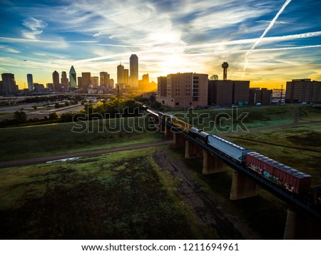 Train crossing Trestles heading towards Dallas , Texas - Sunset sunrise aerial drone view in the North Texas City Skyline cityscape golden hour