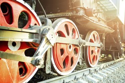 Train drive mechanism and red wheels of an old soviet steam locomotive. Bright rays of the setting sun.