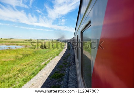 Train goes by rail in summer day, countryside.