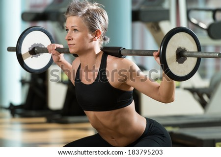 Train Hard Feel Good - Beautiful Fit Woman Doing Barbell Squats In The Gym - stock photo