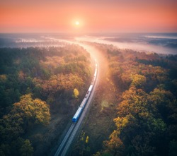Train in beautiful forest in fog at sunrise in autumn. Aerial view of commuter train in fall. Colorful landscape with railroad, foggy trees, orange leaves, red sky and mist. Top view. Railway station