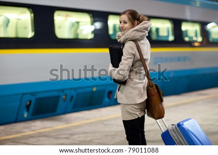Train is coming - young woman waiting for her connection in a modern train station (shallow DOF)