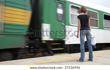 Train is coming - young woman waiting for her connection in a small town train station