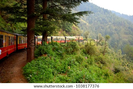 Train moving on mountain slopes, beautiful view, one side mountain, one side valley. Toy train from Shimla to Kalka in India