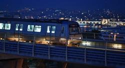 Train of Istanbul subway speeding by bridge on background night city skyline