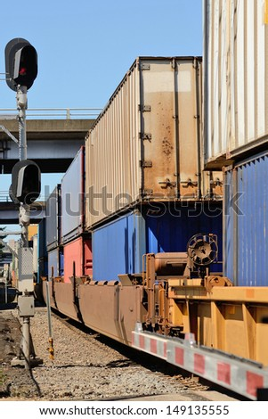 Train passes through an industrial section of a large northwest american city with intermodal modular shipping containers