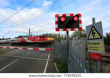Train passing Red lights at an unmanned Level crossing, East Coast Main Line Railway, Peterborough, Cambridgeshire, England, UK