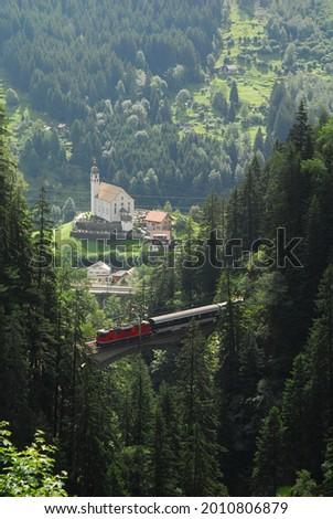Train passing the Gotthard Pass against background of Kirche von Wassen Stock fotó ©