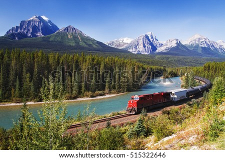Train passing through Bow valley under the surveillance of mighty Rocky Mountains.