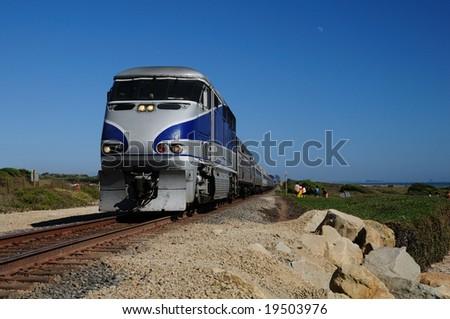 train rushes along tracks on the California coast