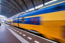 Train speeding up in Amsterdam Central Station.