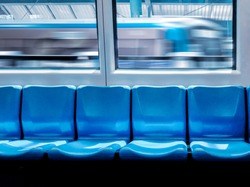 Train station and empty seats commuter with blue color interior inside in the subway train.