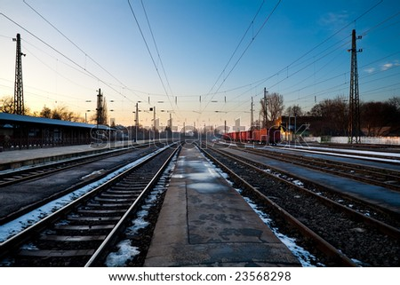 Train station in cold winter at sunset with freight train