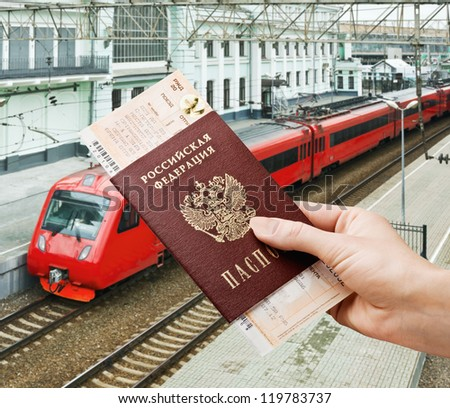 train ticket in his hand against the station