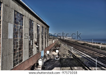Train track by industrial warehouse along coast. freight transport line by the sea in sussex in England