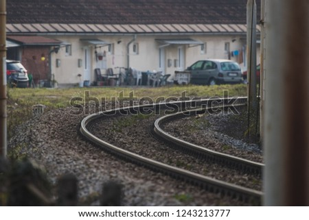 Train track in a sharp curve in urban setting. Decayed neighbourhood pierced with a curved train track.
