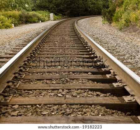Train tracks disappearing around a curve in the trees - stock photo