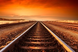 Train tracks goes to horizon in orange majestic sunset.