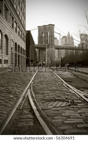 Train tracks on cobblestone road in Dumbo area of Brooklyn, Brooklyn Bridge tower in background, black and white.