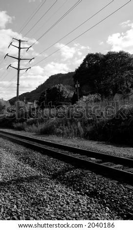 Train tracks pass through rural community; black and white