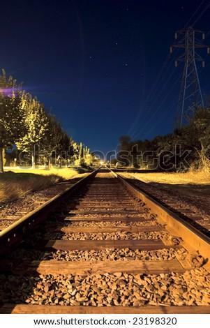 Train tracks under night blue sky