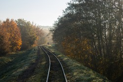 Train tracks winding between autumn colored trees and a man is walking his dog in Anyksciai, Lithuania