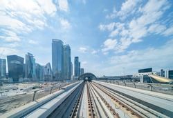 Train view on railway in Dubai Downtown at financial district, skyscraper buildings in urban city, UAE. Transportation for tourists visiting in travel trip or holiday vacation at noon with blue sky.