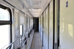 Train wagon inside.  Empty train compartment with a row of closed doors, selective focus, blurred background. Passenger train interior. Comfortable sleeping train compartments. Russian railway