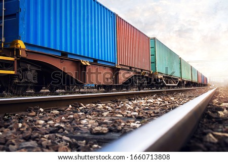 Train wagons carrying cargo containers for shipping companies. Distribution and freight transportation using railroads. Foto stock ©