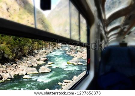 Train window view of a river. Mountain river in Peru.