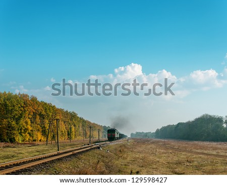 train with smoke over it under cloudy sky