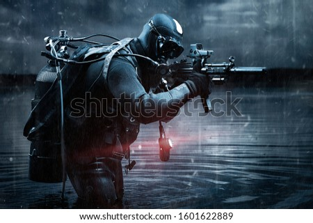 Trained commander of the Marines emerged with a scuba gear and moves to the target with weapons in his hands. The concept of video games, advertising, instability in the world, country conflicts.