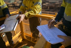 Trained supervisor checking reviewing document issued sign approvals of working at height permit JSA risk assessment on site prior to performing high risk work construction site, Australia