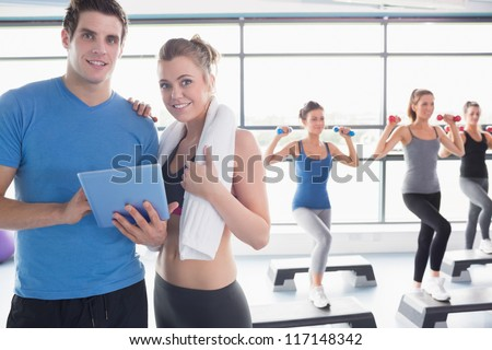 Trainer and woman smiling together during aerobics class in gym
