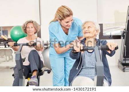 Trainer cares for seniors during ergometer training in rehab