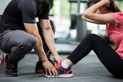 Trainer holding a woman in the leg exercise by Sit-up.