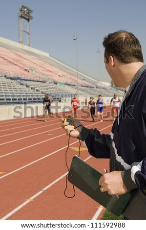 Trainer measuring time while athletes racing
