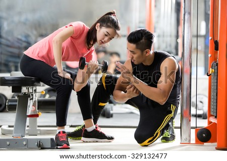 Trainer men are teaching Asian woman lifting a dumbbell. In the way they exercise in the gym.