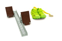 Trainer shoes, starting block and gold medal on isolated white background