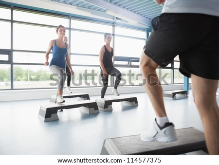Trainer stepping with aerobic class in gym - stock photo
