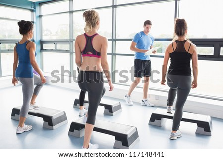 Trainer teaching his aerobic class in gym